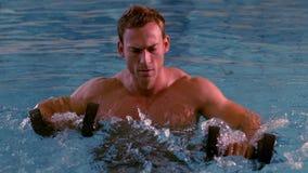 Мышечный человек разрабатывая с гантелями пены в бассейне видеоматериал
