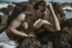 Мышечный, fot парень представляя на море трясет Стоковая Фотография