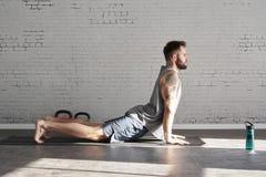 Мышечным тело татуированное спортсменом работая разминку в солнечном спортивном клубе, кирпичной стене Подходящая без рубашки муж стоковые фотографии rf