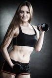 Мышцы плеча тренировки девушки фитнеса поднимая гантели Стоковые Изображения