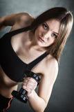 Мышцы плеча тренировки девушки фитнеса поднимая гантели Стоковые Фото