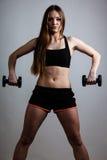 Мышцы плеча тренировки девушки фитнеса поднимая гантели Стоковое Изображение