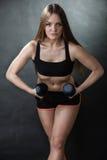 Мышцы плеча тренировки девушки фитнеса поднимая гантели Стоковое Изображение RF