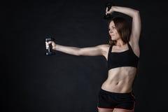 Мышцы плеча тренировки девушки фитнеса поднимая гантели Стоковое Фото