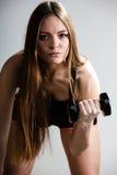 Мышцы плеча тренировки девушки фитнеса поднимая гантели Стоковая Фотография