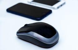 Мышь компьютера беспроволочная и 2 мобильного телефона на белом столе Стоковые Изображения
