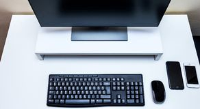 Мышь компьютера беспроволочная, черный монитор, клавиатура и 2 мобильного телефона на белом столе Стоковое Фото