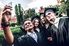 Мы в конце концов градуированное ` ve! Счастливые студент-выпускники стоят в университете внешнем в хламидах усмехаясь и принимая стоковые изображения
