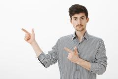 Мы пойдем Портрет уверенно серьезного молодого мужского сотрудника в striped рубашке, указывая с оружием пальца показывать налево стоковое фото rf