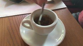 Мы шевелим ложку кофе в малой чашке в кафе сток-видео