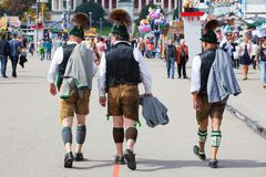 Мюнхен, Германи-сентябрь 27,2017: 3 люд в брюках традиционных баварских одежд кожаных идут на Oktoberfest Стоковое фото RF