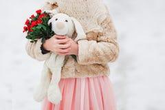 Мягкая игрушка, цветок в руках девушки подарок Весна, зима Стоковое фото RF
