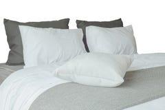 Мягкие белые подушки и удобная кровать на белой предпосылке Стоковое Изображение