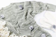 Мягкие, теплые, уютные кардиган, шарф и mittens с конусами ели на белой предпосылке Концепция моды зимы Стоковое фото RF