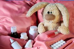 Мягкий кролик болен в кровати с термометром и медициной стоковые фото