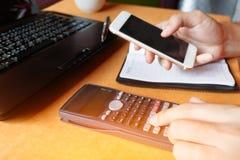 Мягкий фокус, женщина при калькулятор подсчитывая делающ примечания и владение Стоковое фото RF