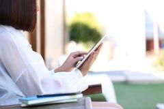 Мягкий фокус прибора планшета удерживания руки женщины умного с печатать стоковые фото