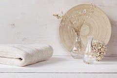 Мягкое домашнее оформление стеклянной вазы с колосками и связанной ткани на белой деревянной предпосылке Стоковое Изображение RF