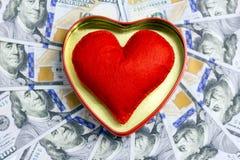 Мягкое сердце в золотой коробке с красным планом на фоне счетов 100-доллара распространило вне в круге Концепция Стоковые Фото
