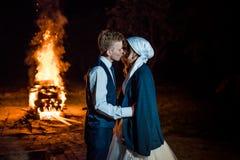 Мягко целовать пар новобрачных на предпосылке горящего огня Невеста носит шаль на ее голове и Стоковые Фотографии RF
