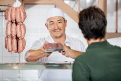 Мясник давая упакованные сосиски к клиенту стоковые изображения rf