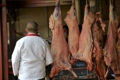 Мясник на базаре воскресенья в Кашгаре, Kashi, Синьцзян, Китае стоковые изображения