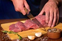 Мясник режет часть свинины стоковое фото rf