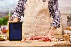 Мясник шеф-повара показывая цифровую таблетку в современном подлинном модель-макете таблетки применения рецепта кухни стоковые изображения