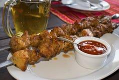 Мясо барбекю на протыкальнике с соусом и стеклом пива в стоковое фото rf
