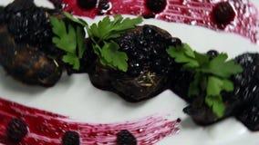 Мясо было положено на белую плиту и было украшено с sause и петрушкой смородины сток-видео