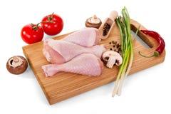 Мясо домашней птицы - ноги и овощи цыпленка на разделочной доске изолированной на белизне Стоковая Фотография