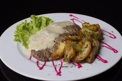 Мясо и зажаренные картошки на белой плите Стоковое Фото