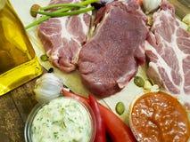 Мясо на деревянной доске перца, масло, соус, гайки, chili, лимон, перец залива, чеснок Стоковые Изображения