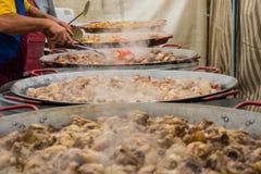 Мясо сварено в больших сковородах и производит пар Подготовка гигантской паэлья стоковое изображение rf