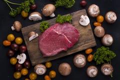 Мясо стейка на черной предпосылке Говядина и овощи и грибы для варить обедающий Открытый космос для текста Взгляд сверху стоковые изображения rf