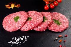 мясо сырцовое палачествуйте бургеров с петрушкой и томатами на черной предпосылке Стоковое фото RF