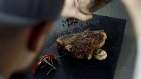 Мясо шеф-повара перча на каменной разделочной доске Руки человека перча зажаренную черту сток-видео