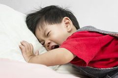 Младенец Азии плача на кровати положил дальше красную рубашку стоковое изображение rf