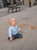 Младенец вползая на улице и усмехаться Стоковая Фотография
