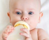 Младенец выпивая от бутылки стоковое изображение
