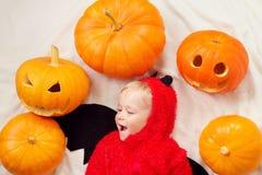 Младенец в костюме дьявола с тыквами Стоковое Изображение