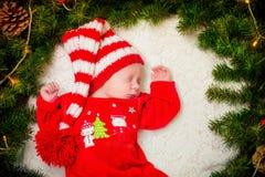 Младенец в красном костюме Санте в венке рождества Стоковое фото RF