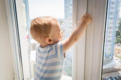 Младенец в опасности Маленький младенец пробуя к открытому окну и вытягивая мимо Стоковое фото RF