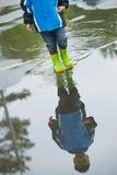 Младенец в резиновых ботинках идя на лужицу Стоковое фото RF