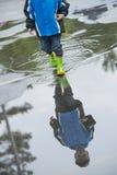 Младенец в резиновых ботинках идя на лужицу Стоковое Изображение