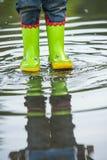 Младенец в резиновых ботинках идя на лужицу Стоковая Фотография RF