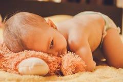 Младенец лежа на кровати и шпионках Стоковое Фото