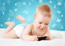 Младенец держа телефон стоковое изображение