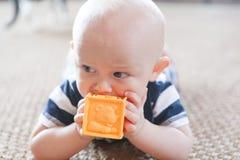 Младенец жуя на блоке игрушки Стоковое фото RF
