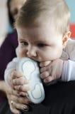 Младенец жуя на ботинках Стоковые Изображения